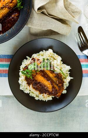 fillet of pink salmon in tomato-coconut sauce in a non-stick frying pan with parsley on a table with a linen tablecloth. healthy family food with basm - Stock Photo
