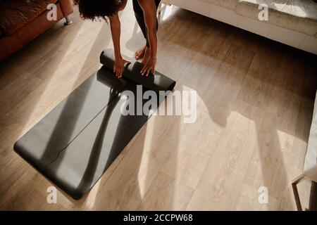 High angle view of young woman standing at home rolling fitness mat after workout