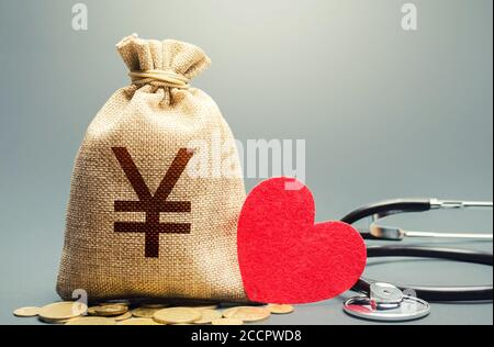 Yen Yuan money bag and stethoscope. Health life insurance financing concept. Funding healthcare system. Reforming and preparing for new challenges. De