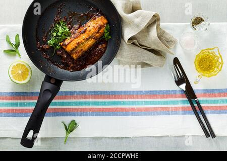 fillet of pink salmon in tomato-coconut sauce in a non-stick frying pan with parsley on a table with a linen tablecloth. healthy family food - Stock Photo