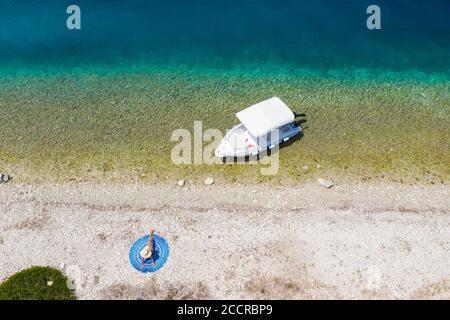 Top down view of a girl sunbathing at Fanari Beach, Meganissi, Ionian Islands, Greece