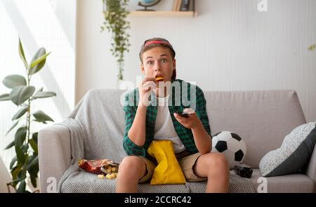 Surprised teenager football fan watching game on tv - Stock Photo