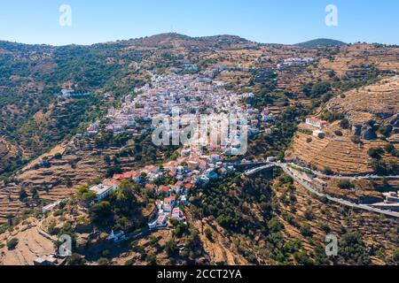 Greece, Kea island. Panoramic aerial drone view of the capital city, Ioulis. Red roofs houses on the rocky mountain landscape - Stock Photo