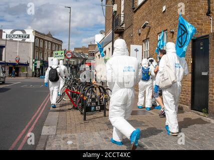 Extinction Rebellion members, dressed in clean suits, march toward Barclays in Balham, to protest the banks continued new investment in fossil fuels.