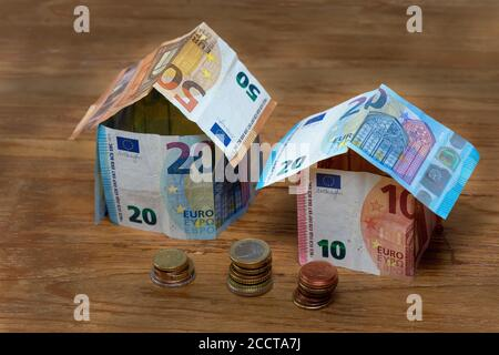 Two houses made of 50, 20 and 10 euro bank notes with stacks of euro coins