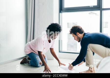 Young multiracial family couple sit on floor in spacious apartment, checking bills, study documents, prepare financial report Family relation and comm