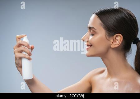 Woman spraying thermal water on her skin Stock Photo
