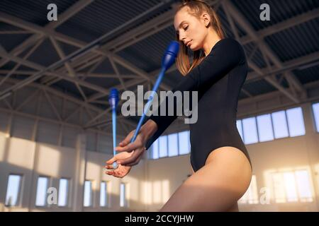 Charming beautiful girl training in storts hall, keeping dark blue gymnastics clubs in hands,looks down, shot from below, active lifestyle concept - Stock Photo