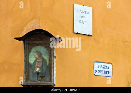 a poetic glimpse on piazza Santo Spirito heart of the popular San Frediano district of Florence with a small tabernacle in the foreground