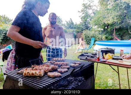 Chicken meat on skewers and pork steaks on a charcoal grill. Barbecue in the back yard garden. - Stock Photo