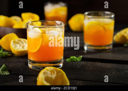 Homemade lemon iced tea glass on dark background. A refreshing summer drink made of fresh hand squeezed lemon mixed with cold black tea, ice and sugar - Stock Photo