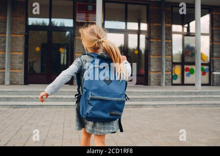 Cute little girl with backpack running back to school Stock Photo