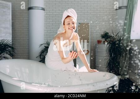 Morning routine of redhead joyful beauty in the bathroom. Playful Woman having fun while running bath, splashing the water at camera. - Stock Photo
