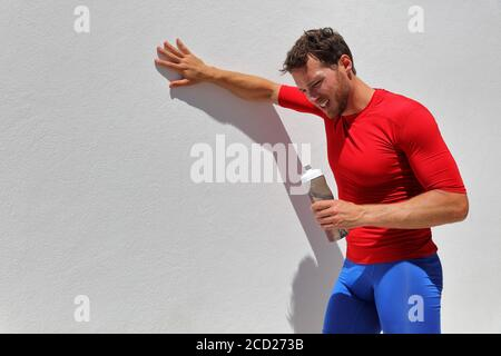 Tired exhausted dehydrated man runner drinking water bottle after workout. Running person taking a break after run. Fitness athlete breathing from sun - Stock Photo