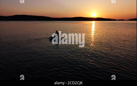 A man in an inflatable boat floats on the sea at sunset - Stock Photo