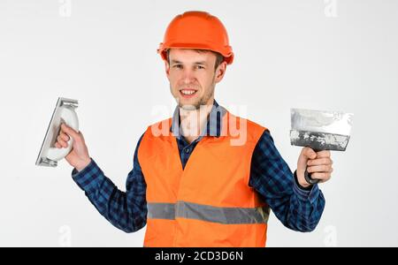 transfer of experience. young worker is engineer assistant. repairman in uniform. man use spatula tool. real construction worker in helmet. carpenter ready to work. building tool repair equipment. - Stock Photo