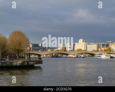 View along the River Thames over Waterloo Bridge to Shell Mex House, 80 Strand, and Charing Cross Station in winter under grey skies