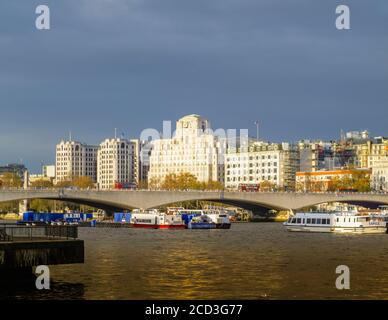 View across the River Thames over Waterloo Bridge to Shell Mex House in morning light in winter under grey skies