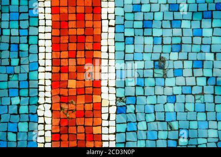 Blue and turquoise and red old antique mosaic tiles on the bottom of the fountain as a background.