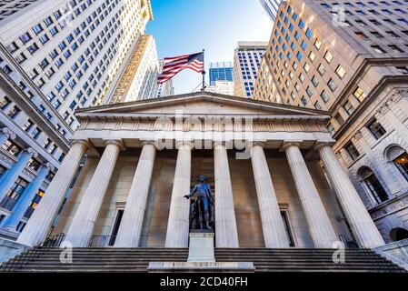 Famous Wall Street and the building of Federal Hall with patriot flag in New York, United States. Stock Photo