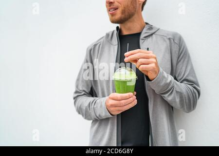 Healthy young man drinking green juice smoothie cup as weight loss detox meal replacement diet. Spinach protein shake for morning breakfast Stock Photo