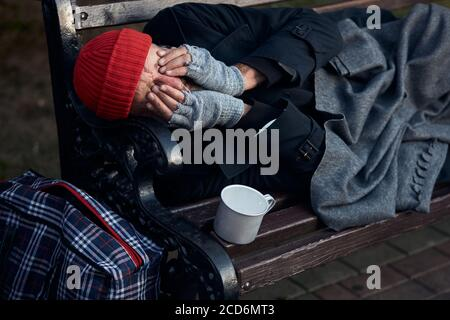 Penniless senior man lying on park bench, trembling from the cold, closed face with hands. Cup for collecting money, coins next to him.