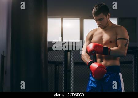 Young athletic man preparing for boxing competitions, training defense and attacks in fighting club, making punches in red boxing gloves and moving ar - Stock Photo