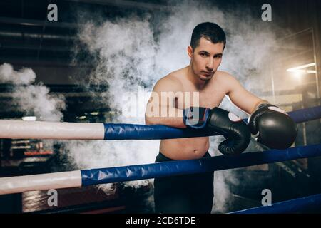 young caucasian boxer man stand wearing protective boxer gloves isolated over smoky ring. Man with sportive muscular body in full combat readiness to - Stock Photo
