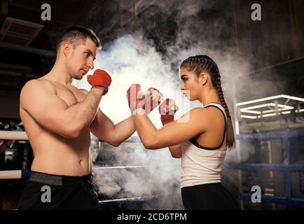 combat readiness of caucasian man and woman in ring, fit sportive couple boxing together, wearing red protective gloves