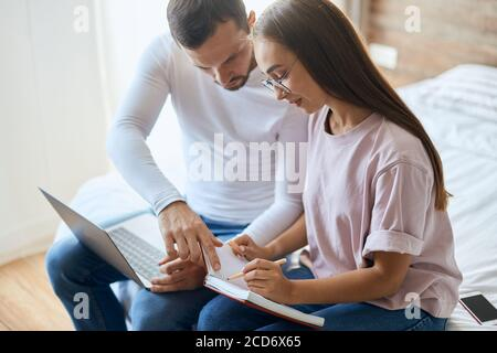 Toung pleasant woman in optical specticals with long beautiful hair, discussing plans for vacation together with young boyfriend, keeping note book on
