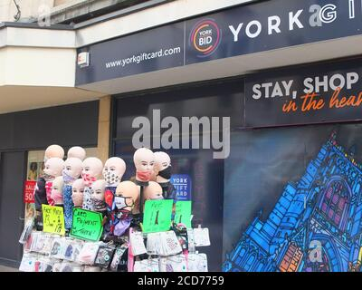 Street market stall with mannequin heads selling a variety of face coverings and masks to protect from spreading Coronavirus in York, UK - Stock Photo