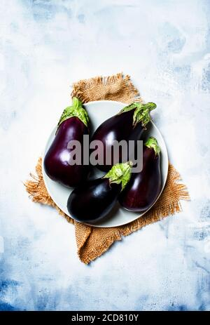 Fresh purple eggplants on plate, stone background, top view Stock Photo