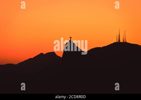 The famous Rio de Janeiro landmark - Christ the Redeemer statue and Corcovado mountain silhouette by sunset - Stock Photo