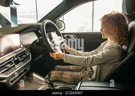 attractive curly caucasian child girl sit inside of new car, she likes this car, want parents to make purchase in dealership