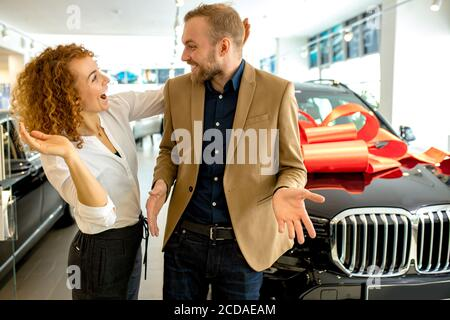 beautiful caucasian lady make surprise to husband in dealership. woman give new car wrapped in red bow to her husband, birthday gift. she openes man's - Stock Photo