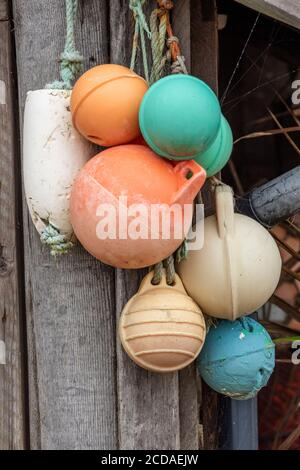 a number of buoys tied together in a fishing harbour coloured fishing markers in a nautical or maritime setting. - Stock Photo