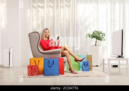 Young blond woman sitting in an armchair with a mobile phone and shopping bags in a living room - Stock Photo