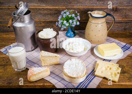 Milk in a jug and a glass, different sorts of cheese, whipped cream, curd, and a piece of butter in a rustic scenery on a wooden table with a kitchen - Stock Photo