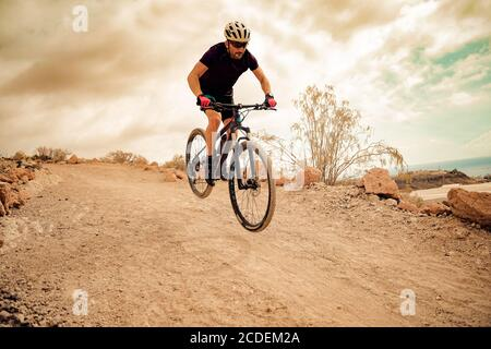 Cyclist in violet t-shirt Riding a mountain bike. Man on mountain bike rides on the trail on a stormy day. Extreme Sport Concept - Image