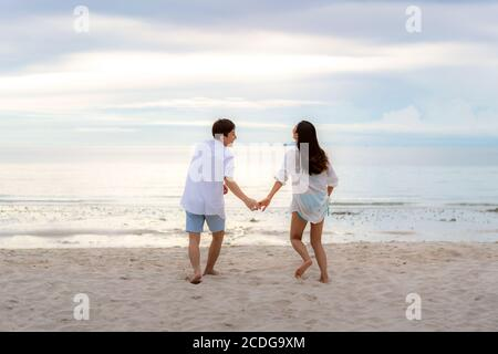 Asian couple in love having romantic tender moments running and hand hold on the beach between sunset in Thailand. - Stock Photo