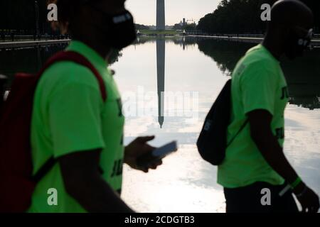 Protesters begin to gather in front of the Lincoln Memorial on the National Mall before the beginning of civil rights march organized by Al Sharpton to call attention to systemic racism and police violence after the May police killing of George Floyd in Minnesota, in Washington, D.C., on August 28, 2020, amid the coronavirus pandemic. The night before The Commitment March: Get Your Knee Off Our Necks, protests consumed the blocks surrounding the White House, as President Trump gave his presidential nomination acceptance speech with sounds from noisy demonstrations in the background. (Graeme Sl - Stock Photo