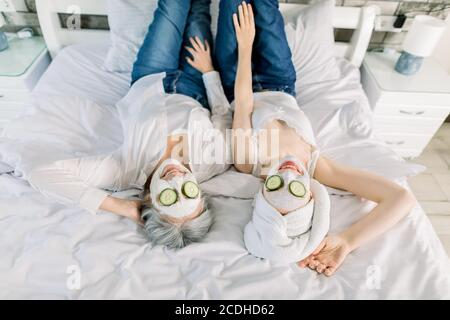 Top angle view of two charming women, senior gray haired lady and young girl with towel on head, lying on the bed and enjoying spa day with face masks