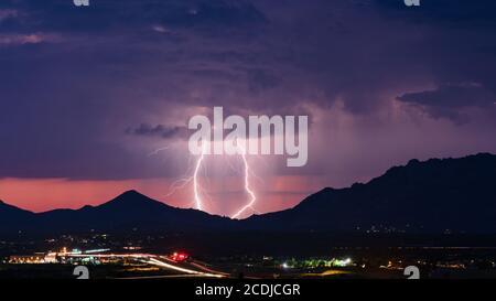 Lightning bolts from a monsoon storm illuminates the evening sky over Prescott, Arizona.