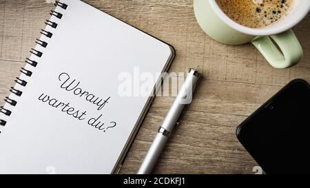 Worauf wartest du? German text. Translatiion: what are you waiting for? Flat lay. Work space with a note pad, ball pen, mobile and a cup of coffee. - Stock Photo