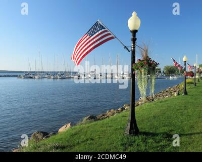 The U.S. flag flies proudly from lampposts along a sunny lakefront near a marina.