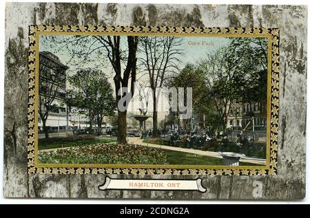 The postcard features individuals seated on benches in Gore Park in downtown Hamilton with the fountain in the background. The coloured image is inset with a gold leaf pattern border and an second border that is abstract.   Postcard Collection HPL_PC_s18_69r_32022206615524 - Stock Photo