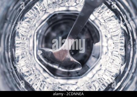 Metal teaspoon in a faceted glass cup with reflection, top view, close-up. Gray and blue abstract background, futuristic wallpaper, transparent surfac