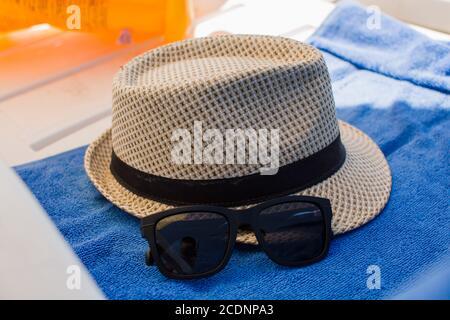 a mens beach hat on sun lounger - Stock Photo