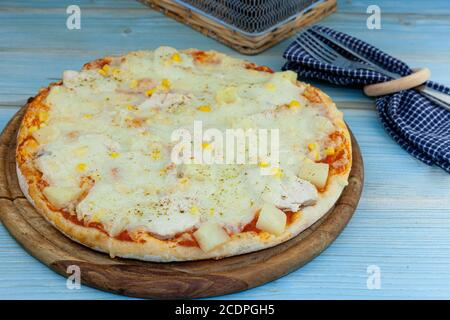 Traditional pizza on a wooden tray on the table. Round pizza with chicken, corn, pineapple, cheese. Homemade baking. Fork, knife, blue background