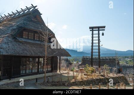 Thatched roof house with bell beside in the old Japanese village called Saiko Iyashino-Sato Nenba (Healing Village).
